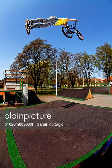 Teenager doing BMX bike stunt in skateboard park, Osijek, Croatia, Europe