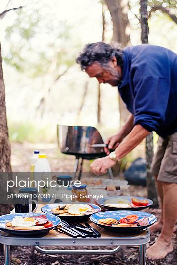 Senior man preparing dinner during camping