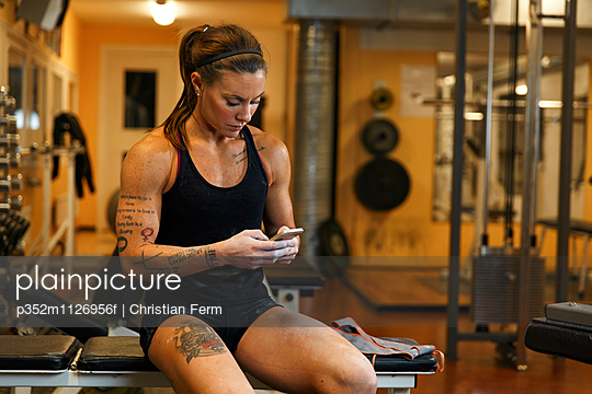 Sweden, Woman using mobile phone in gym