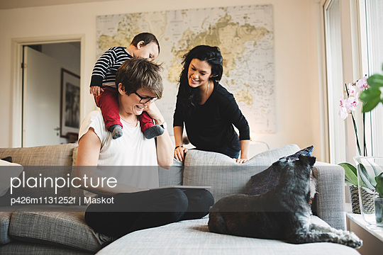 Mother carrying daughter watching digital tablet with woman at home