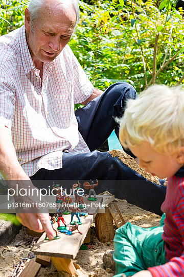 Junge und Großvater spielen mit Figuren in einem Sandkasten, Freital, Sachsen, Deutschland - p1316m1160765 von Roetting+Pollex