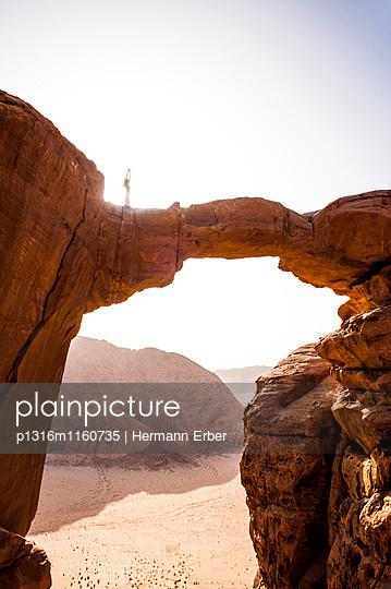 Frau in einer Yogaposition auf Felsbrücke über den Jabal Burdah, Wadi Rum, Jordanien, Naher Osten - p1316m1160735 von Hermann Erber