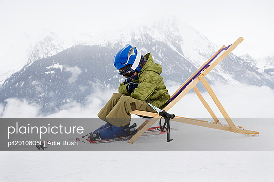 Child with skis sitting on deck chair