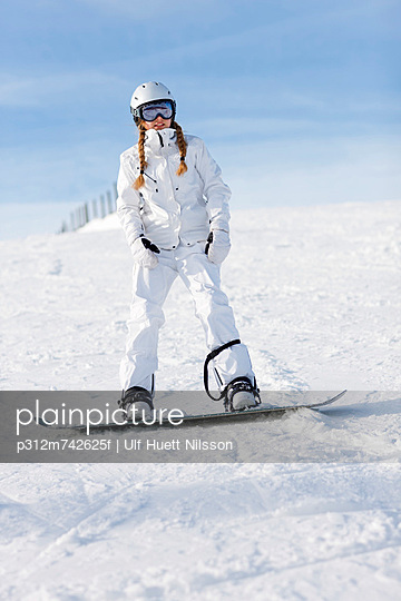 Teenage girl snowboarding