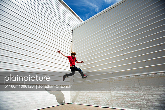 Young man practicing parkour against wall