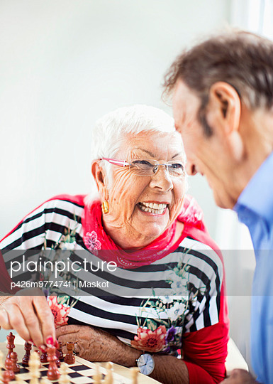 Happy senior couple looking at each other while playing chess in nursing home