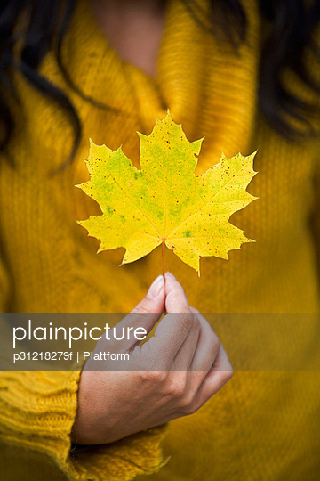 A woman holding an autumn leaf Sweden.