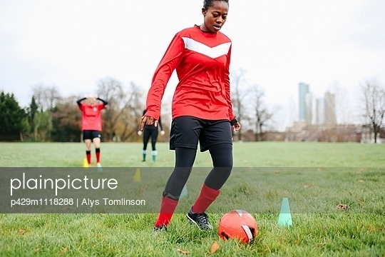 Young woman soccer player practicing with soccer ball in park