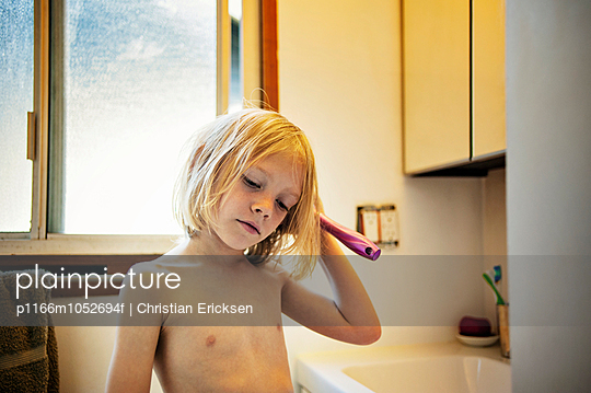 Thoughtful shirtless boy combing hair in bathroom