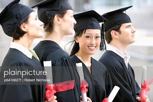 Graduates in caps and gowns holding diplomas