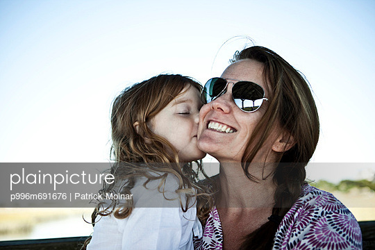 Portrait Of Little Girl Kissing Her Mother On The Cheek