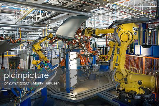 Robots handling car parts in car factory