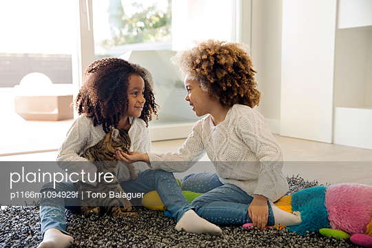 Two girls playing with cat at home