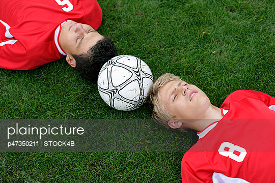 Soccer player lying head to head on grass, football between them