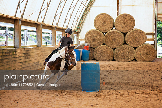 Boy riding horse in ranch