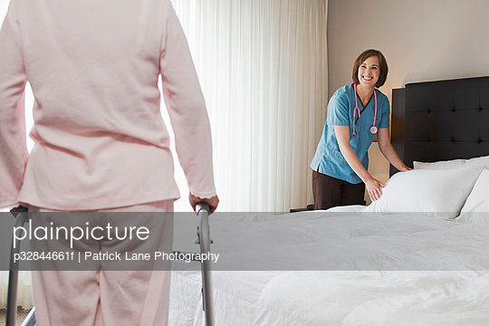 Nurse making bed in patient\'s bedroom