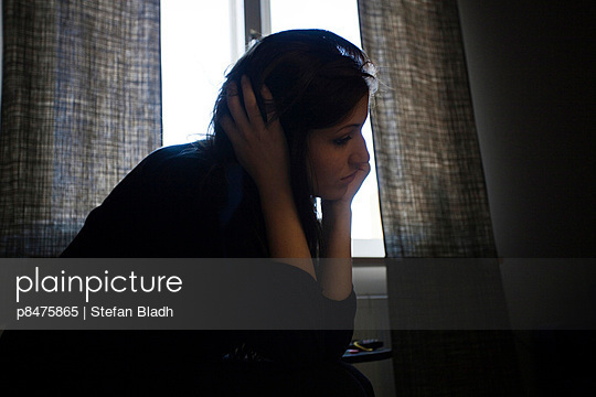 Depressed young woman sitting on the bed in her room