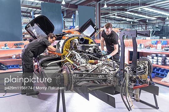 Engineers repair car in racing car factory