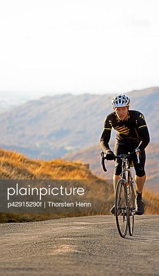 Man biking along rural road