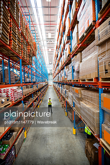 Portrait of a warehouse manager in an aisle of a warehouse