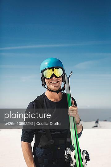 Portrait of happy mature man in ski-wear on snowy field