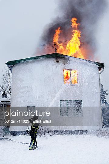 Fireman spraying water on burning building
