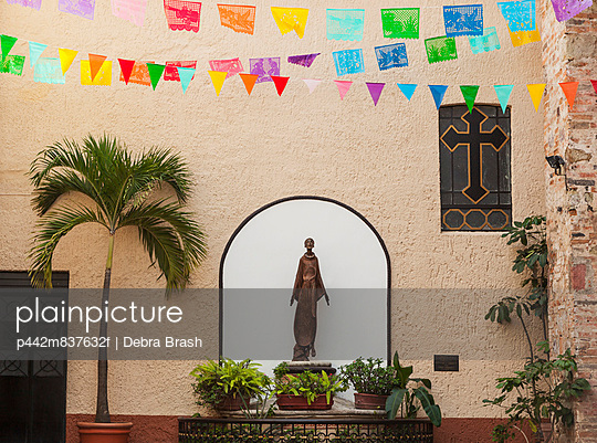 A sculpture of san francisco de assisi is sheltered by the church of our lady of guadalupe;Puerto vallarta mexico