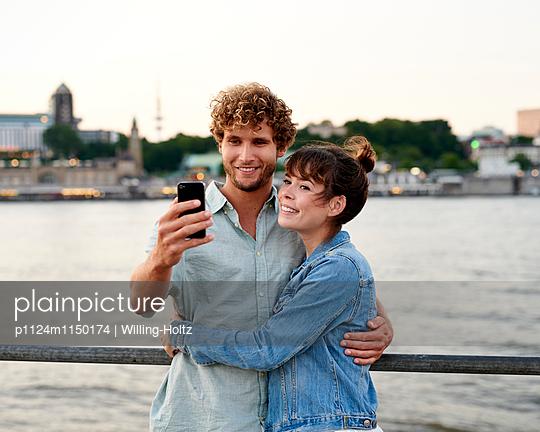 Paar macht Selfie an der Elbe - p1124m1150174 von Willing-Holtz