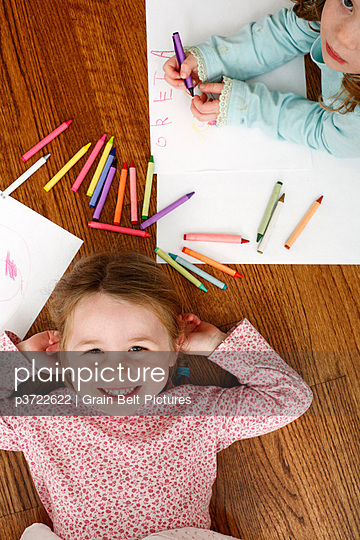 Downward view of young girl laying next to artwork and crayons