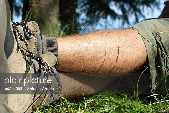 Man in hiking boots relaxing on grass with legs crossed, low section