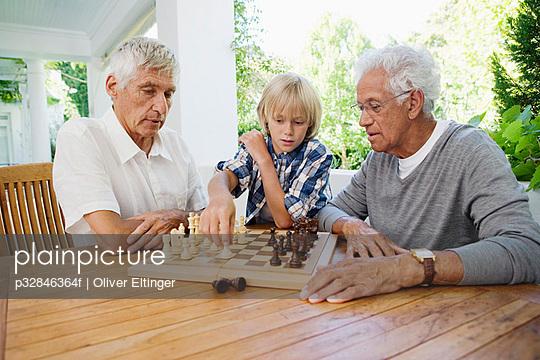 Pair of senior men playing chess while boy (10-12) is watching