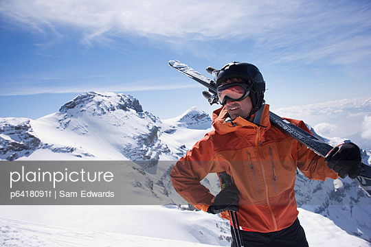 Man carrying his skis on a mountain