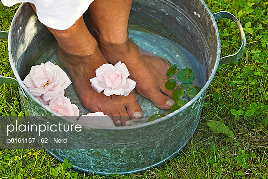 Woman with feet in zinc bowl with rose petals