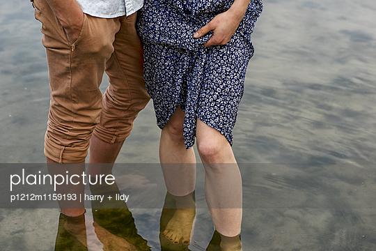 Unterkörper eines Jungen Paares im Wasser  - p1212m1159193 von harry + lidy