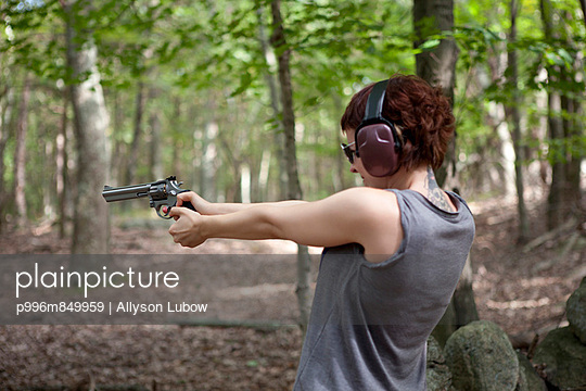 Woman shooting pistol in forest.