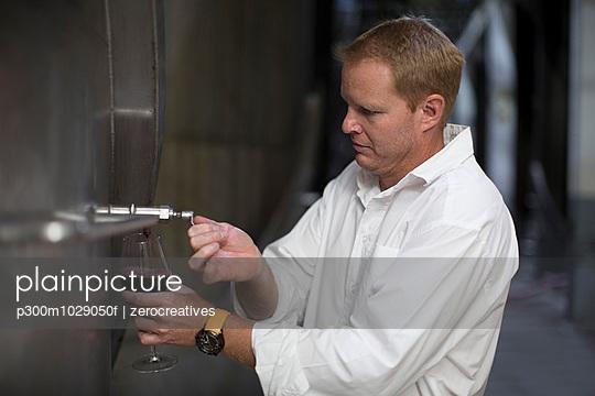 Winemaker testing wine from vats