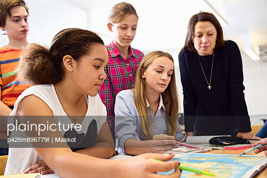 Teacher with students studying map at desk in classroom