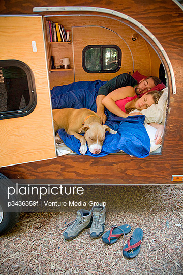 A young couple with their dog camping in a trailer near Big Sur