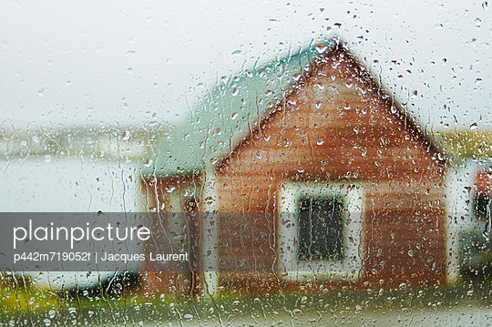 Rain on a window with a view of a fishing hut outside; newfoundland, canada