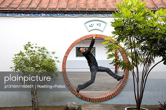 Deutscher Tourist im Mondtor eines Tempels, Tainan, Republik China, Taiwan, Asien - p1316m1160451 von Roetting+Pollex