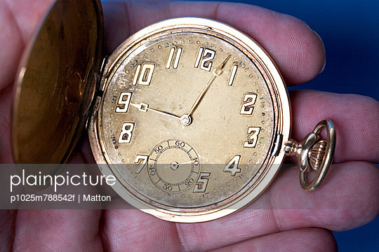 Close-up of a hand holding an antique pocket clock against blue background