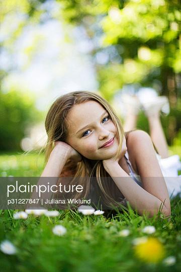 Girl lying on lawn, smiling, portrait