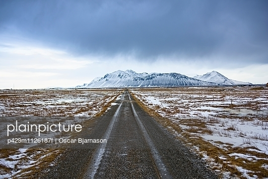 Diminishing perspective of road on snow covered scrubland to snow capped mountain, Alftaneshreppur, Iceland