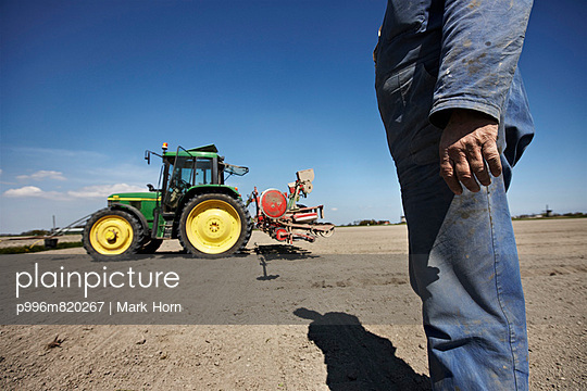 Farmer Standing On Field Tractor In Background