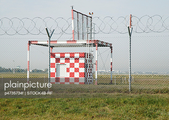 Weather station on airfield behind chain-link fence