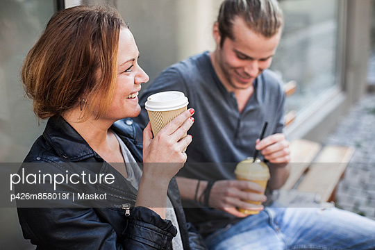 Happy woman drinking coffee in disposable cup with man on bench at sidewalk