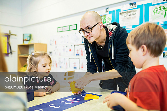 Male teacher assisting students in art class at kindergarten