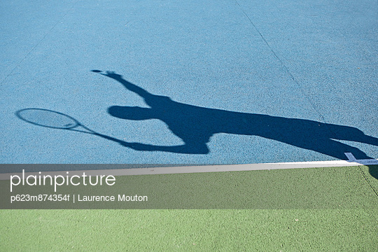 Shadow of tennis player serving ball