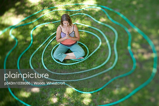 A woman meditates in the middle of a coiled garden hose in Hailey, Idaho.