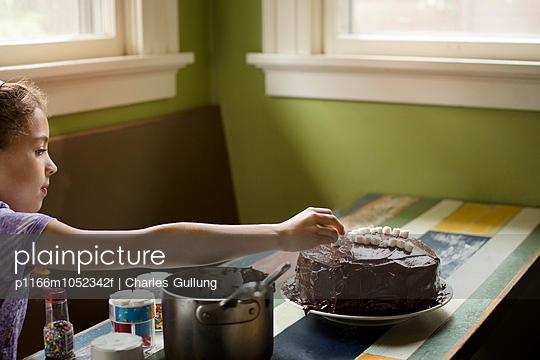 Girl (10-11) decorating cake